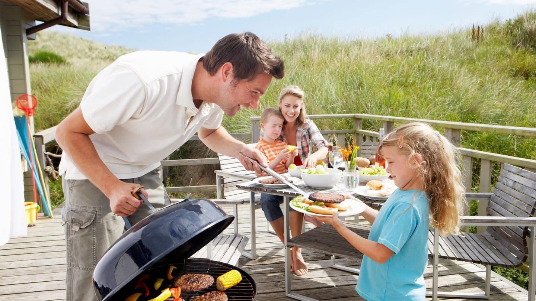 Eine Familie grillt. Der Mann gibt seiner kleinen Tochter ein Steak. Auf dem Grill liegen Grillfleisch und Mais. Frau und Sohn sitzen am Tisch im Hintergrund.