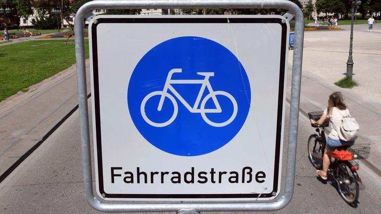 Auf einem blauen Schild mit weißem Hintergrund ist ein Fahrrad abgebildet. Darunter steht der Schriftzug Fahrradstraße. Neben dem Schild fährt eine Radfahrerin vorbei. (Foto: picture-alliance / Reportdienste, Uli Deck/dpa)