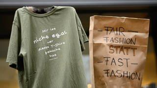 """Demonstranten halten in Stuttgart ein T-Shirt mit der Aufschrift """"Mir ist nicht egal wer dieses T-Shirt gemacht hat"""" und eine Tüte mit der Aufschrift """"Fair Fashion statt Fast Fashion"""" hoch. (Foto: dpa Bildfunk, picture alliance/Sina Schuldt/dpa)"""