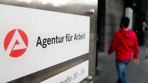 Ein Mann geht hinter dem Schild der Agentur für Arbeit in Stuttgart zum Eingang. (Foto: dpa Bildfunk, picture alliance / Sebastian Kahnert/dpa)