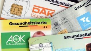 Gesundheitskarten verschiedener Krankenkassen liegen auf einem Tisch. (Foto: dpa Bildfunk, picture alliance/Jens Kalaene/dpa-Zentralbild/dpa)