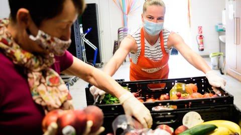 Zwei Mitarbeiterinnen sortieren in einem Tafelladen Lebensmittel (Foto: picture-alliance / Reportdienste, Picture Alliance)