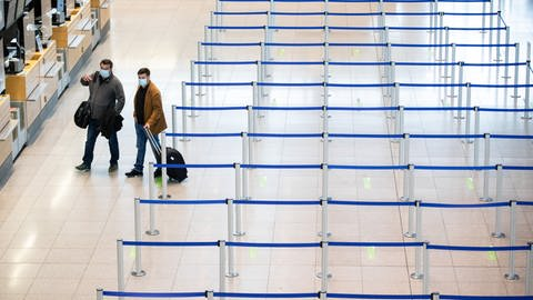 Zwei Fluggäste laufen am Flughafen Stuttgart durch das Terminal. (Foto: dpa Bildfunk, Christoph Schmidt)