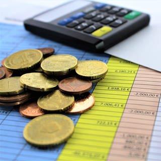 Auf einer Übersichtstabelle liegt Kleingeld, im Hintergrund ein Gerät für Online-Banking. (Foto: Colourbox, X28460681)