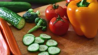 Paprike, Gurkenstücke und Tomaten auf einem Schneidbrett (Foto: dpa Bildfunk, Picture Alliance)