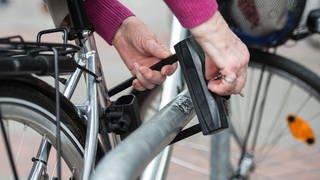 Eine Frau schließt ein Fahrrad mit einem Fahrradschloss an. (Foto: dpa Bildfunk, picture alliance / Silas Stein/dpa | Silas Stein)