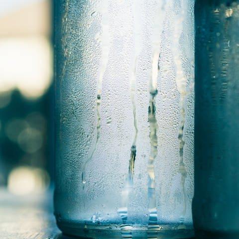 An zwei gläsernen und angeschlagenen Wasserflaschen laufen Tropen runter. (Foto: greg-rosenke-B_8AakaXD48-unsplash)
