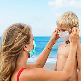 Mutter setzt Sohn am Strand Gesichtsmaske auf. (Foto: Colourbox)