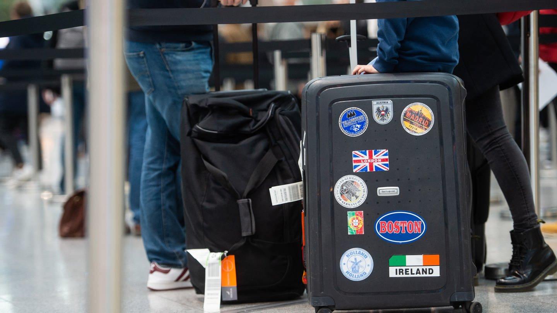 Famile am Flughafen mit Koffer, auf dem UK-Flagge zu sehen ist.