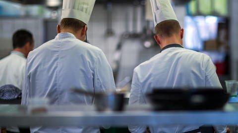 Zwei Auszubildende mit Kochmützen sind von hinten zu sehen (Foto: dpa Bildfunk, Picture Alliance)