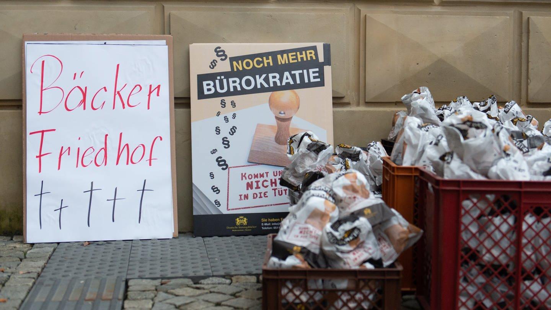 Brötchentüten und Plakate stehen vor einem Gebäude. (Foto: dpa Bildfunk, picture alliance/Lucas Bäuml/dpa)