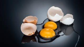 Zwei aufgeschlagene Eier liegen auf einem Tisch. Das Eiweiß ist rund um das Eigelb verteilt, diie Eierschalen liegen daneben. (Foto: Colourbox)