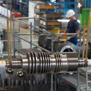 Ein Arbeiter steht in einer Montagehalle des Siemens-Turbinenwerks. Im Vordergrund hängt eine Turbine in der Montage. (Foto: dpa Bildfunk, picture alliance/Sebastian Kahnert/zb/dpa)