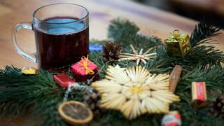 Ein Glas roter Glühwein steht neben einem Weihnachtsgesteck. (Foto: dpa Bildfunk, picture alliance / Arno Burgi/dpa-Zentralbild/dpa)