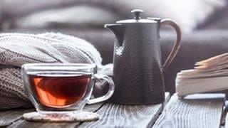Eine Teetasse und Teekanne stehen auf einem Tisch im Hintergrund ist ein Wohnzimmer zuerkennen. (Foto: Getty Images, Thinkstock -)