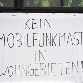 An einem Haus in der Gemeinde Elchesheim-Illingen hängt ein Transparent auf dem steht «Kein Mobilfunkmast in Wohngebieten». (Foto: dpa Bildfunk, picture alliance / dpa/Uli Deck)