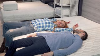 Paar liegt i einem Geschäft auf einer Matratze (Foto: Colourbox)