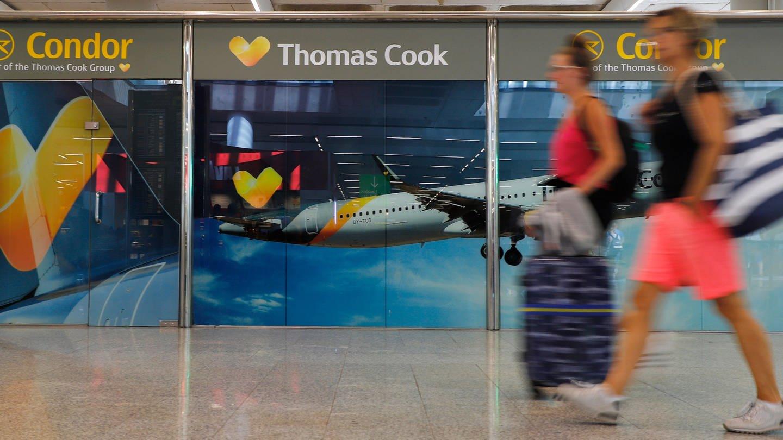 Passagiere gehen neben einem großen Werbeschild von Thomas Cook am Flughafen von Palma de Mallorca. (Foto: dpa Bildfunk, Clara Margais)