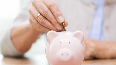 Seniorin wirft Geld in ihr Sparschwein. (Foto: Getty Images, Thinkstock - dolgachov)
