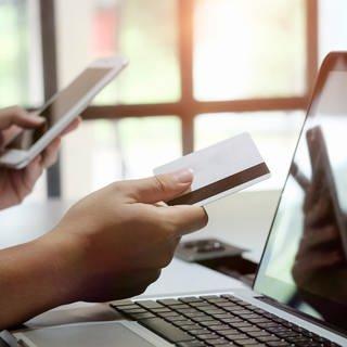 Symbolbild: Eine Person sitzt mit Smartphone und EC-Karte vor einem Laptop (Foto: Colourbox, Prathan Chorruangsak)