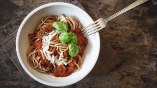 Teller mit Vollkornspaghetti und Tomatensoße mit Mozarella und Basilkumblättern. (Foto: Imago, imagoimages)