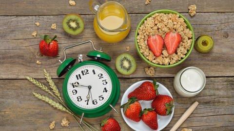Verschiedene Frühstückszutaten und ein Wecker stehen auf einem Tisch (Foto: Colourbox)