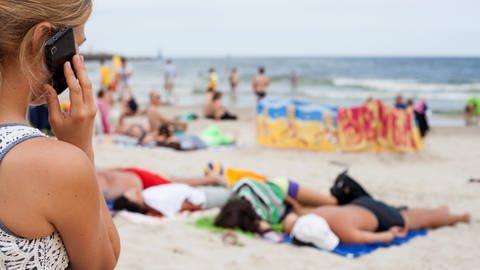 Ein Frau sitzt an einem Strand und hält ein Handy ans Ohr. (Foto: dpa Bildfunk, picture alliance / Daniel Naupold/dpa)