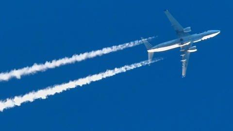 Ein Flugzeug mit Kondensstreifen ist am blauen Himmel zu sehen. (Foto: dpa Bildfunk, picture alliance/Patrick Pleul/dpa-Zentralbild/dpa)