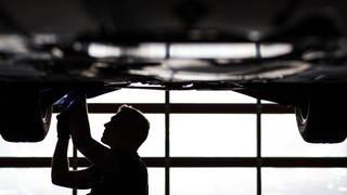 Mechaniker arbeitet in einer KfZ-Werkstatt an der Unterseite eines Autos (Foto: dpa Bildfunk, Foto: David-Wolfgang Ebener/dpa)