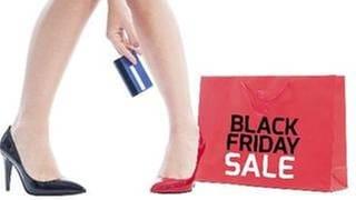 Zwei Frauenbeine mit unterschiedlichen Schuhen, dazu eine Hand mit Kreditkarte und ein Shoppingbag mit der Aufschrift Black Friday Sale (Foto: Getty Images, Thinkstock -)