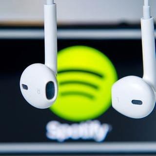 Kopfhörer hängen  vor einem Apple Iphone 5s, auf dem das Logo vom Musik-Streaming-Dienst Spotify angezeigt wird (Foto: picture-alliance / dpa, picture-alliance / dpa -)