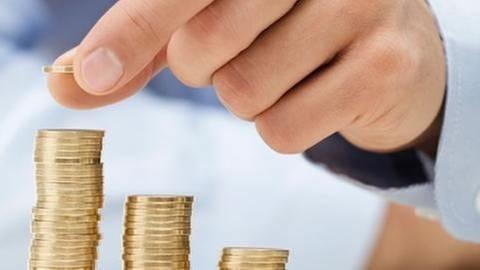 Ein Mann legt eine Münze von einem Stapel auf einen anderen Stapel Münzen. (Foto: Getty Images, Thinkstock -)