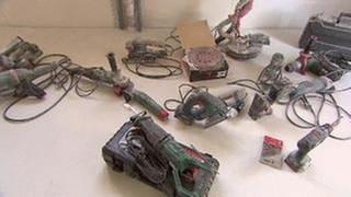 Mehrere Werkzeuge liegen auf einer Baustelle. Schleifmachine, Akkuschrauber, Schlagbohrer und weitere Geräte liegen auf dem Boden. (Foto: SWR, SWR -)