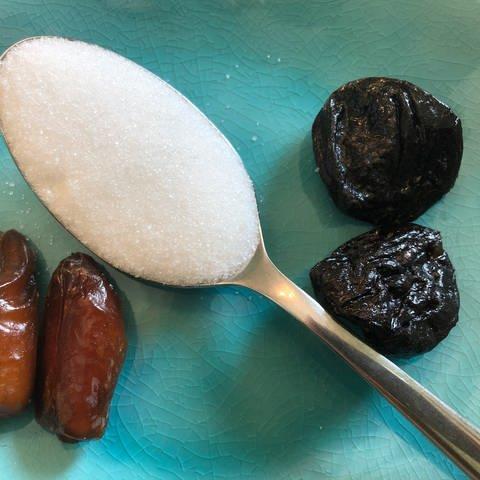 Je zwei getrocknete Datteln und Pflaumen liegen mit einem Esslöffel Zucker auf einem Teller (Foto: SWR, Sabine Schütze)