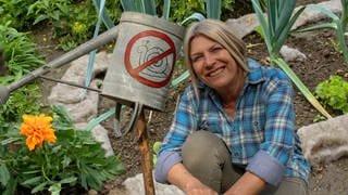 Frau mit blondem Pagenkopf in Garten mit Gießkanne, die durchgestrichenes Schneckenbild zeigt (Foto: SWR)