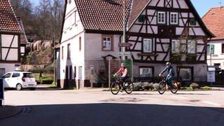 Tatjana Geßler und ein Mann auf Fahrrädern in Rumbach unterwegs (Foto: SWR)
