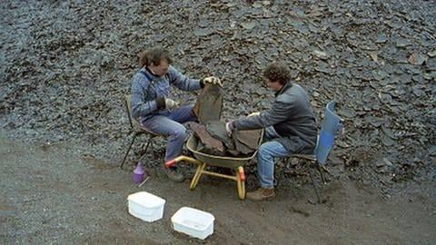 Zwei Männer sitzend mit Schieferplatten (Foto: SWR, SWR/Telepool -)