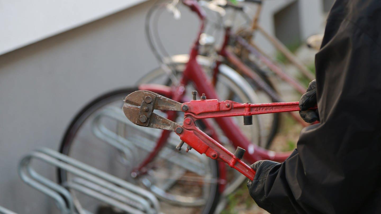 Bolzenschneider in der Hand eines Diebes vor einem Ständer mit Fahrrädern. Gute Fahrradschlösser können vor Fahrraddiebstahl schützen.